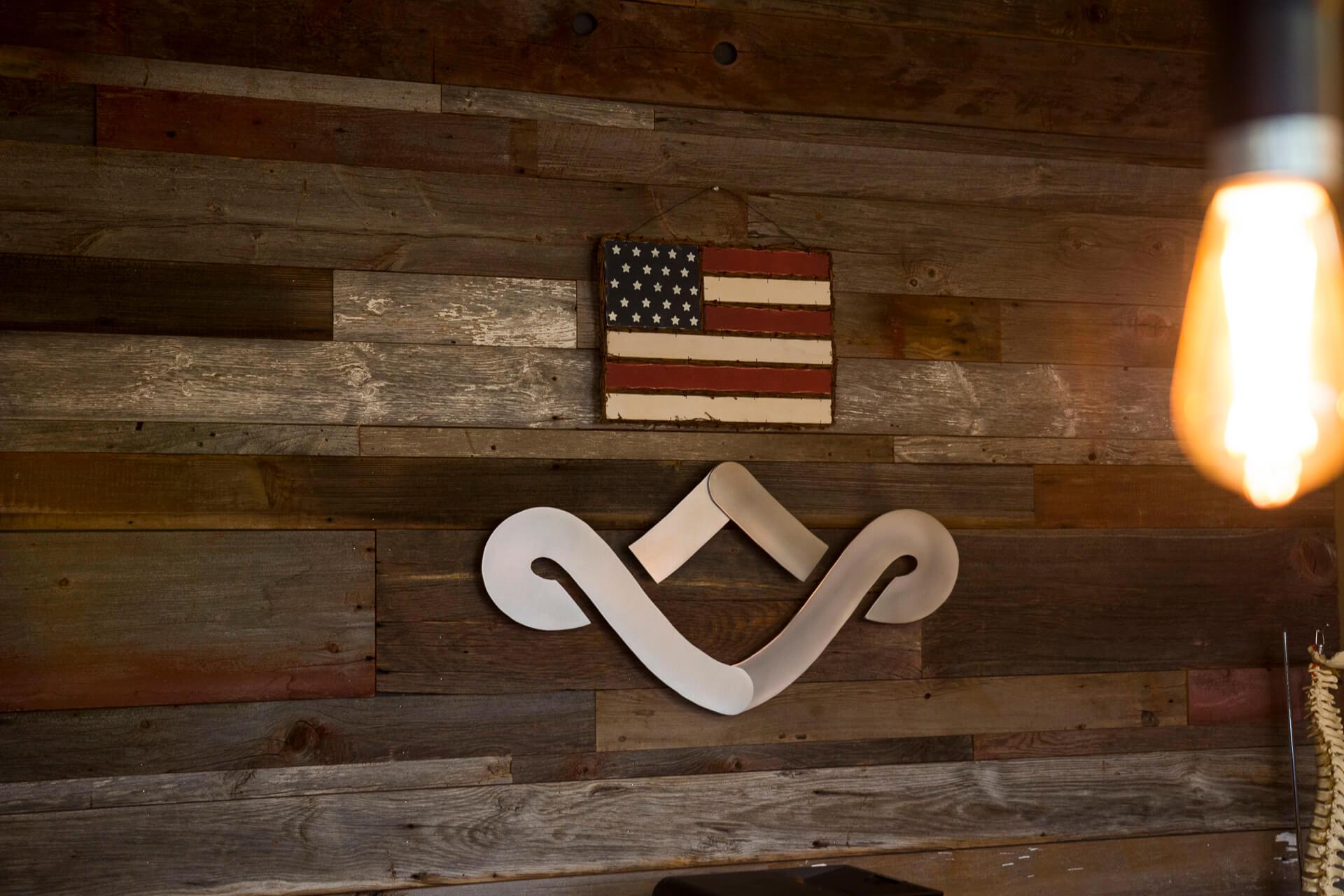 Logo and American flag on barn wood wall
